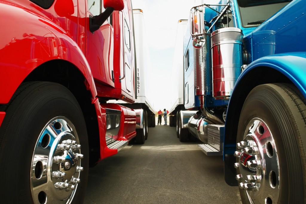 Truck drivers standing in between trucks at truck stop
