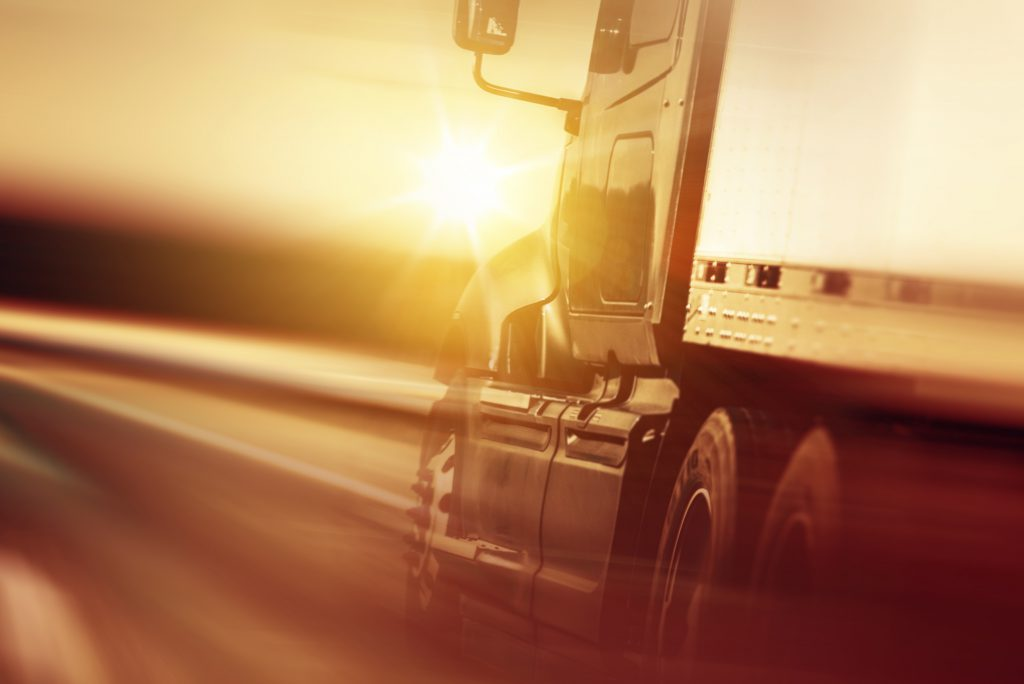 Semi Truck In Motion. Speeding Truck on the Highway. Trucking Business Concept